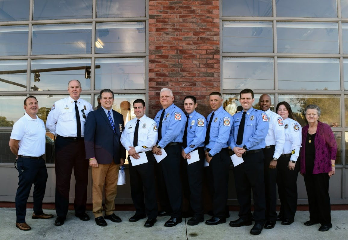 From left, Darren Gray, Carle Bishop, Jimmy Patronis, the seven firefighters and Gail Ash stand in front of the fire station for a photo.