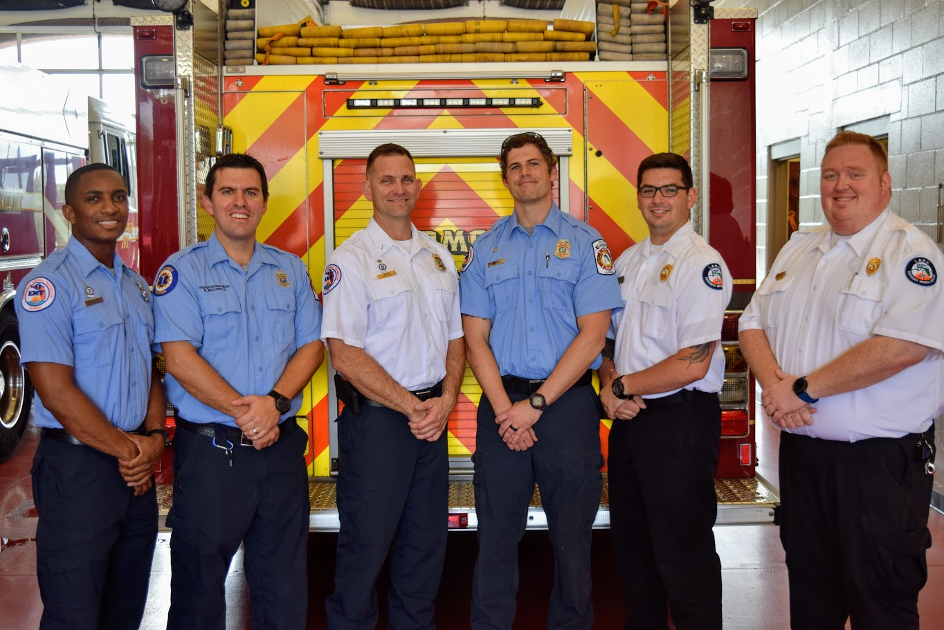 Firefighters stand smiling in front of a firetruck