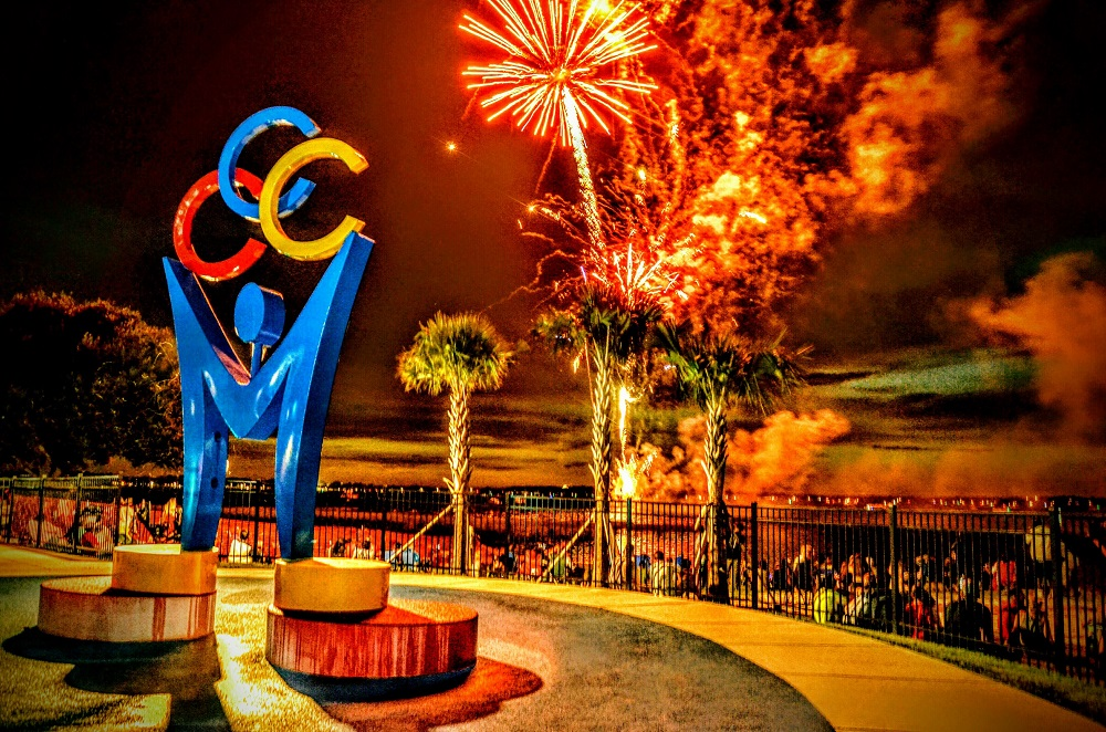 Fireworks show in front of the splash pad in waterfront park with the Clermont rings sculpture in the center.
