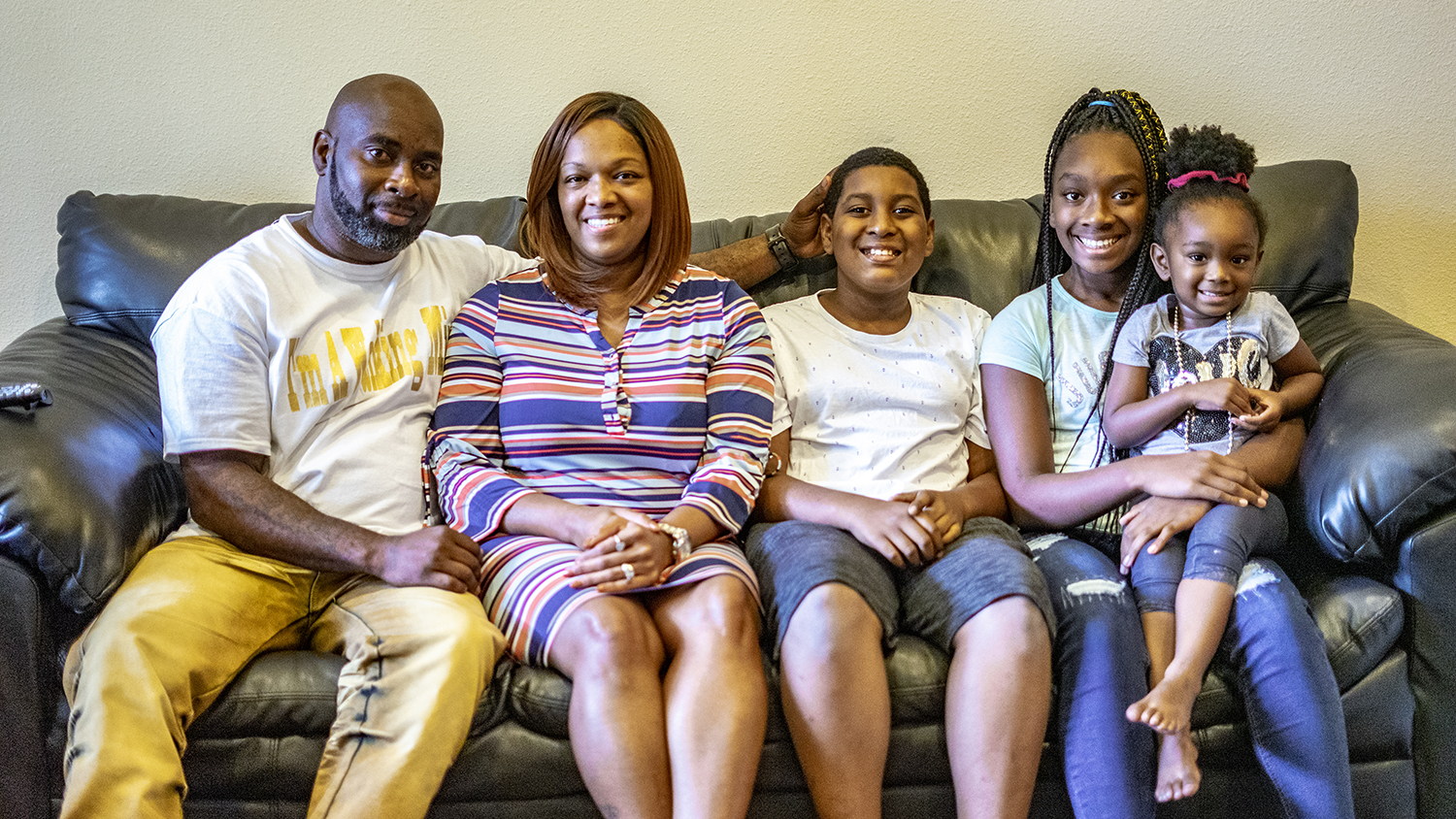 the survivor, his wife and children sit on a couch smiling
