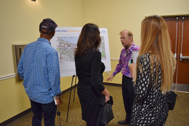 IT Director Don Dennis speaks to three attendees about Clermont's Master Plan while standing next to a display board about the Master Plan on an easel.
